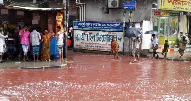 In this Tuesday, Sept. 13, 2016 photo, people wade past a road turned red after blood from sacrificial animals on Eid al-Adha mixed with water from heavy rainfall in Dhaka, Bangladesh. Authorities in Dhaka had assigned several places in the city where residents could slaughter animals, but the heavy downpours Tuesday meant few people could use the designated areas. (AP Photo)
